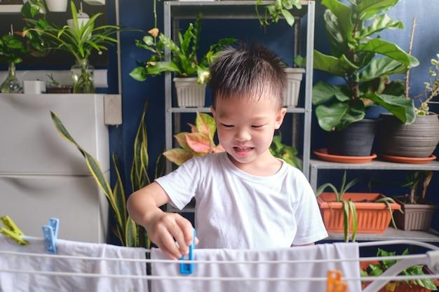 Piccolo bambino asiatico sveglio divertendosi ad appendere vestiti lavati puliti su stendino per asciugare a casa