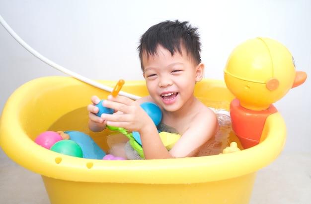 Piccolo ragazzo asiatico sveglio del bambino che prende un bagno da solo da solo nel bagno a casa