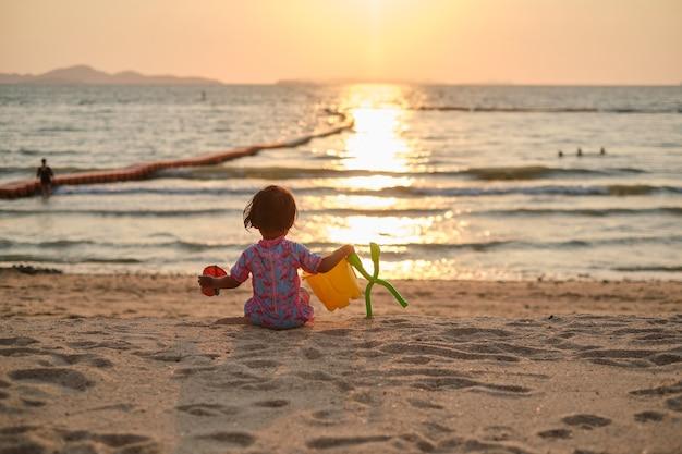 Carina bambina asiatica che gioca con i giocattoli da spiaggia sulla spiaggia tropicale durante le vacanze estive