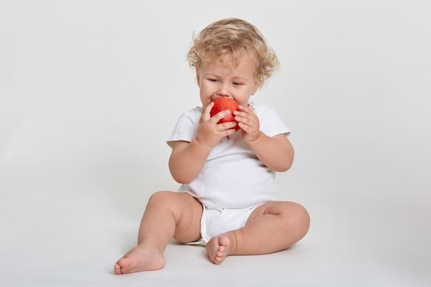 Piccolo bambino sveglio nel vestito del corpo che morde nella mela matura rossa mentre si siede a piedi nudi sul pavimento isolato sopra lo spazio bianco