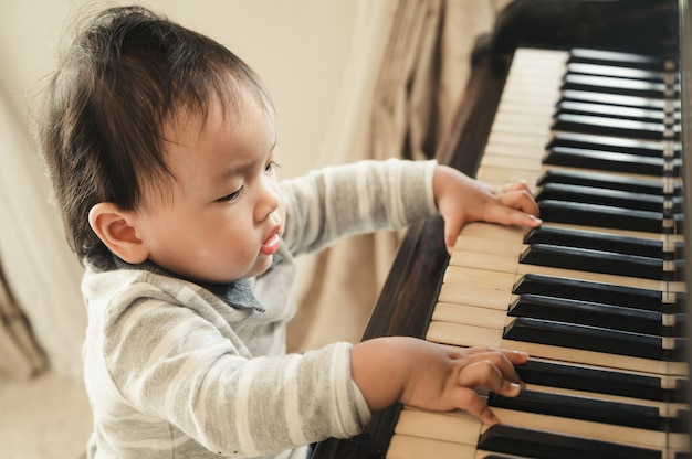 Il piccolo neonato sveglio suona il pianoforte a casa