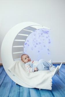Piccolo neonato sveglio sul letto di legno bianco sotto forma di mezzaluna contro le luci di natale blu