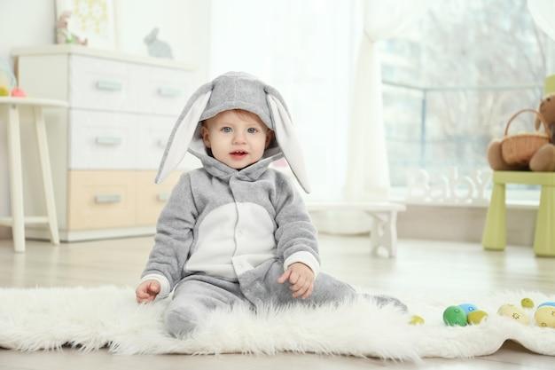 Simpatico bambino in costume da coniglio che gioca a casa