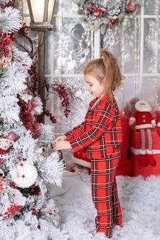 Piccola neonata sveglia che decora l'albero di natale all'interno. buon natale concetto.