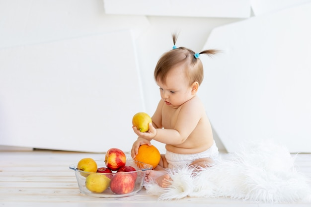 Piccola neonata sveglia che mangia frutta