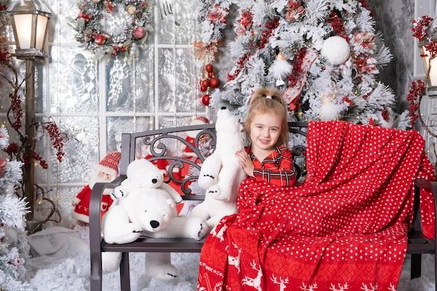 Piccola neonata sveglia che si diverte nella stanza decorata di natale. buon natale concetto.
