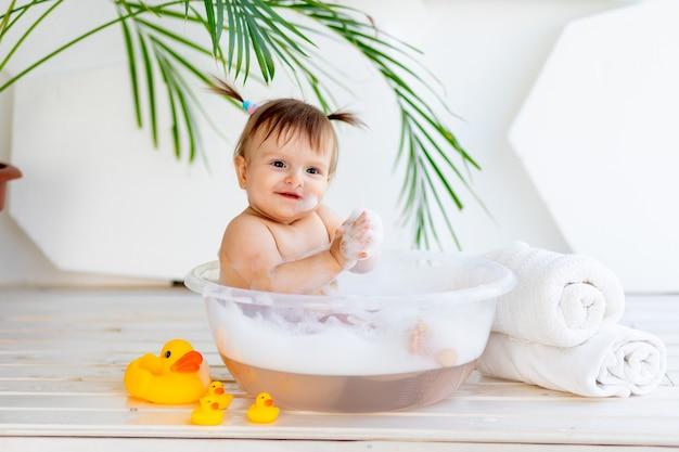Piccola neonata sveglia che cattura un bagno