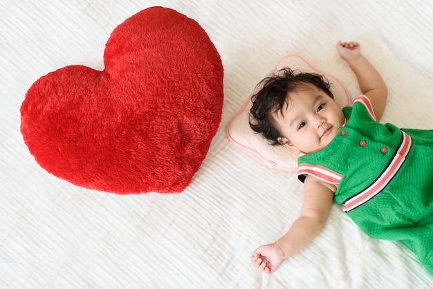 Una piccola bambina carina indossa un abito verde sdraiato accanto a un cuscino a forma di cuore rosso sul letto