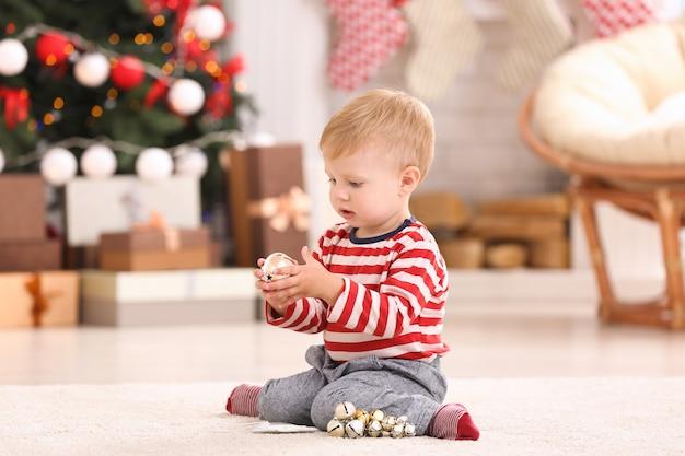 Simpatico bambino che gioca con le decorazioni natalizie a casa