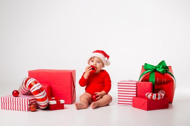 Piccolo bambino sveglio in un costume della santa con i regali