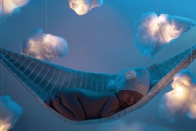 Piccolo bambino sveglio che dorme sull'amaca con molte nuvole fatte di cotone idrofilo