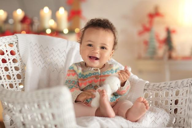 Simpatico bambino sulla sedia di vimini su superficie sfocata