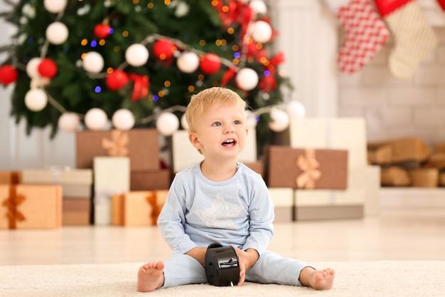 Piccolo bambino sveglio con l'orologio a casa. concetto di conto alla rovescia di natale