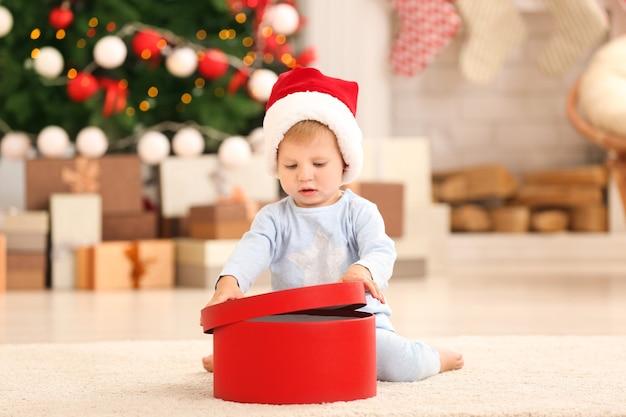 Simpatico bambino con confezione regalo in camera decorata per natale