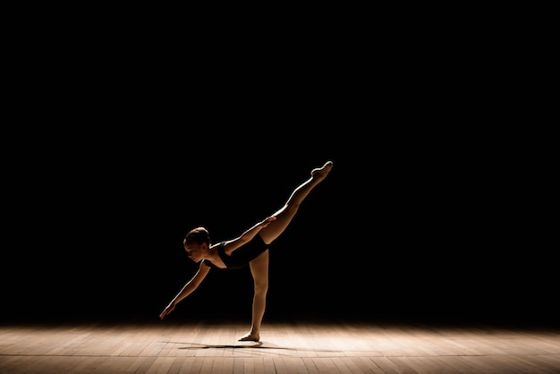 Piccola ballerina sveglia in costume da balletto scuro che balla sul palco. kid in classe di danza. la ragazza del bambino sta studiando il balletto.