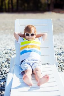Piccolo ragazzo biondo sveglio in occhiali da sole si siede su un lettino sulla costa dell'oceano