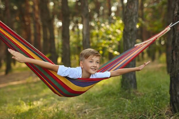 Carino piccolo ragazzo caucasico biondo che si diverte con un'amaca multicolore nel cortile o nel parco giochi all'aperto. tempo libero estivo attivo per bambini. bambino sull'amaca. attività e divertimento per i bambini all'aria aperta