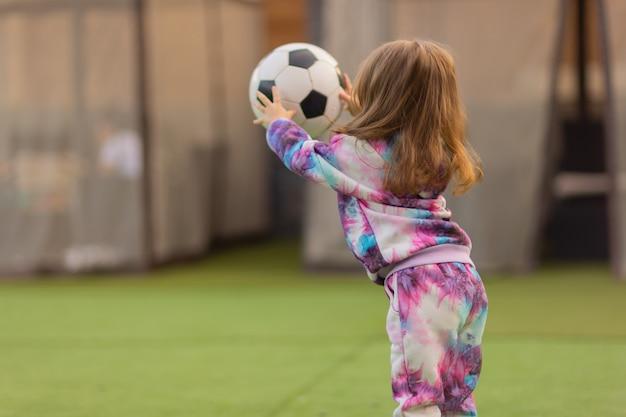 Piccola ragazza bionda sveglia in camicia rosa che lancia ridendo del pallone da calcio.
