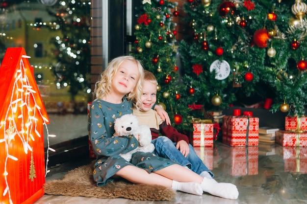 Piccolo fratello e sorella biondi svegli che posano all'albero di natale