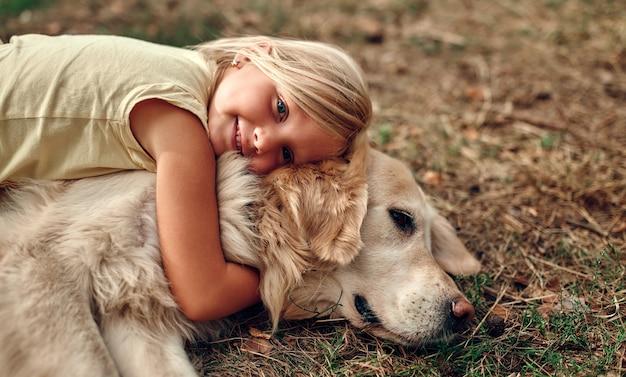 Una graziosa bambina bionda giace sull'erba abbracciando il suo amico un cane labrador.