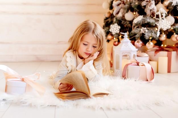 La piccola ragazza bionda sveglia legge un libro a casa vicino all'albero di natale