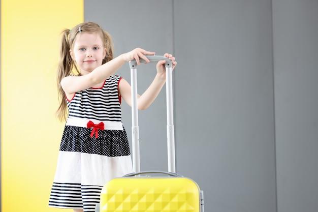 La piccola ragazza bionda sveglia sta con la valigia gialla