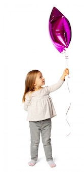 Piccola ragazza bionda sveglia con baloon a forma di stella porpora isolato su fondo bianco