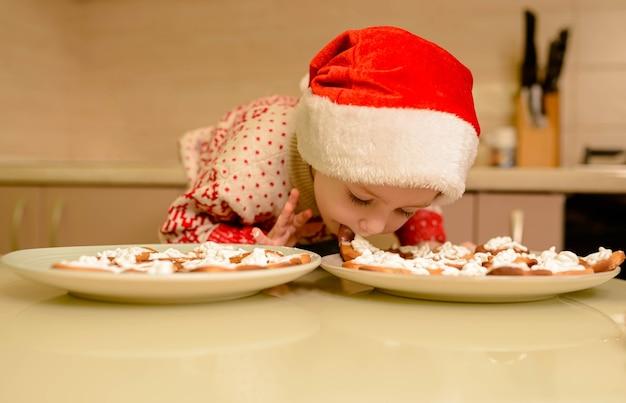 Il ragazzino sveglio cuoce i pan di zenzero festivi fatti in casa. ragazzo divertente in cappelli di santa helper che producono i biscotti. bambino che cucina i biscotti di natale a casa.