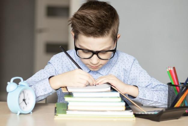Ragazzino sveglio che fa i compiti. scuola del nemico di apprendimento del bambino.