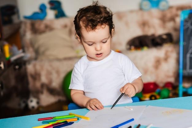 Un ragazzino carino disegna nel suo album da disegno con matite colorate