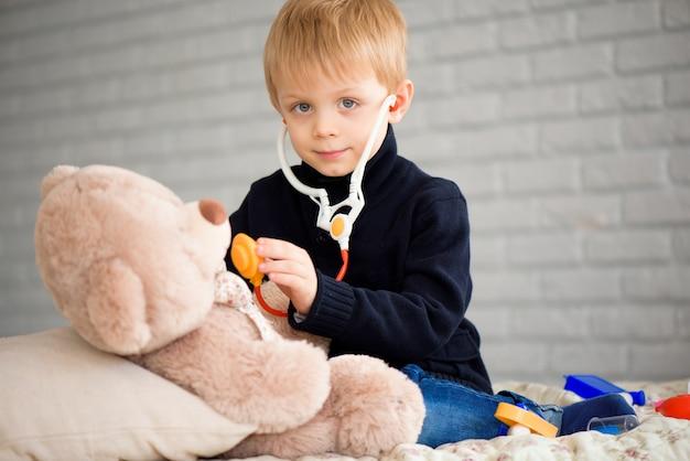 Ragazzino sveglio vestito come medico che gioca con l'orso del giocattolo a casa.