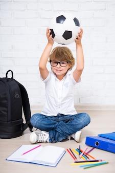 Ragazzino carino con gli occhiali con gli strumenti della scuola e il pallone da calcio a casa