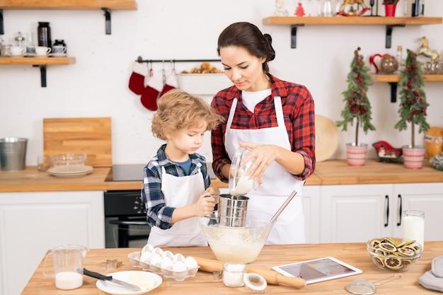 Ragazzino sveglio che aiuta sua madre a setacciare la farina mentre prepara l'impasto per la pasticceria fatta in casa in cucina nel fine settimana