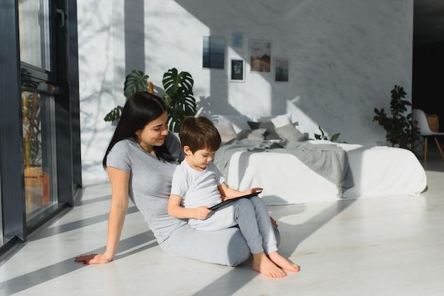 Ragazzino sveglio e sua madre giovane utilizzando una tavoletta digitale e sorridente sul pavimento a casa.