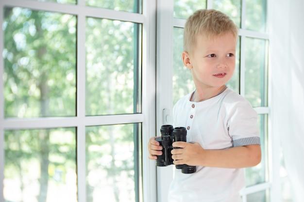 Ragazzino sveglio che tiene binocolo nero e distoglie lo sguardo dalla fotocamera.