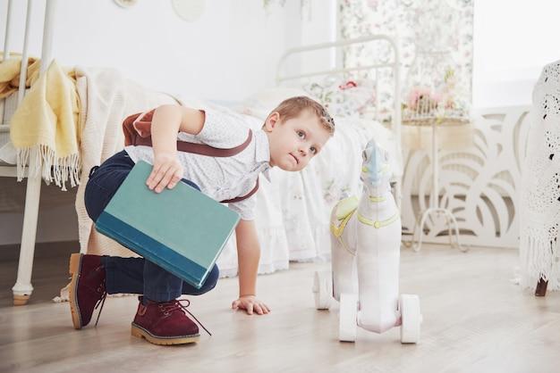 Il ragazzino carino sta andando a scuola per la prima volta. bambino con zaino e libro. il bambino fa una valigetta, stanza dei bambini. di nuovo a scuola