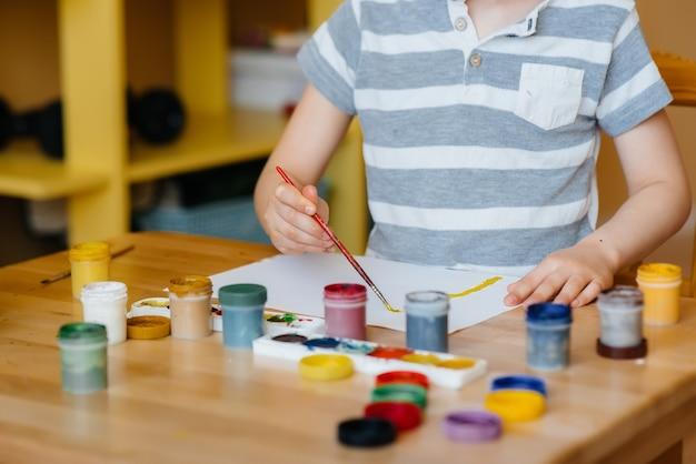 Un ragazzino carino sta giocando e dipingendo nella sua stanza. ricreazione e intrattenimento. resta a casa.