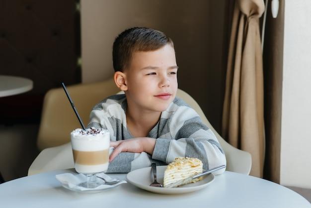 Un ragazzino sveglio è seduto in un caffè e guarda una torta e un primo piano di cacao. dieta e corretta alimentazione.