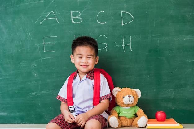 La scuola materna sveglia dell'asilo del ragazzino in uniforme dello studente con il sacchetto di scuola si siede con l'orsacchiotto sulla lavagna verde della scuola