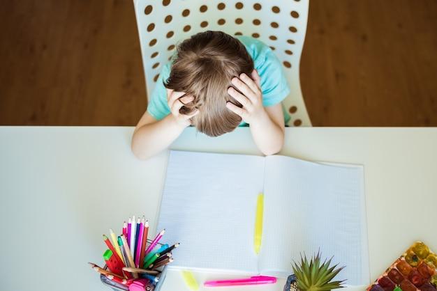 Ragazzino sveglio che dipinge con le matite colorate a casa, all'asilo o all'asilo. giochi creativi per bambini che stanno a casa