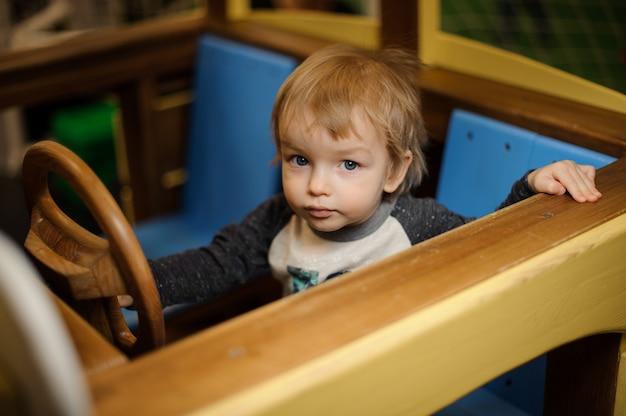 Ragazzino sveglio che gioca nell'automobile di legno del giocattolo