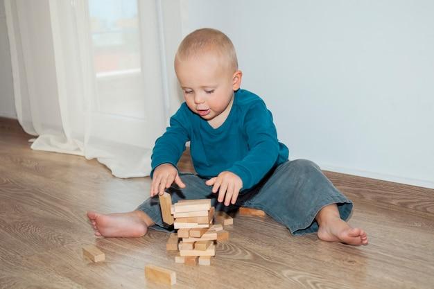 Ragazzino sveglio che gioca con i cubi di legno sul pavimento. concetto infanzia felice e gioco educativo.