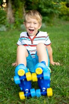Un simpatico ragazzino in pattini a rotelle è seduto sull'erba il concetto di giochi attivi sportivi
