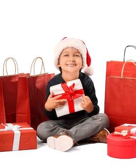Ragazzino sveglio in cappello della santa, con scatole regalo e borse della spesa isolate