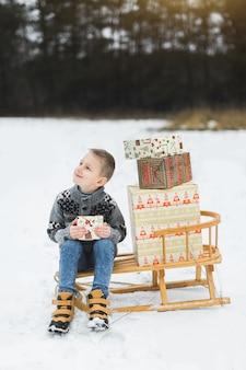 Ragazzino sveglio, seduto su una slitta di legno decorata con scatole di regali