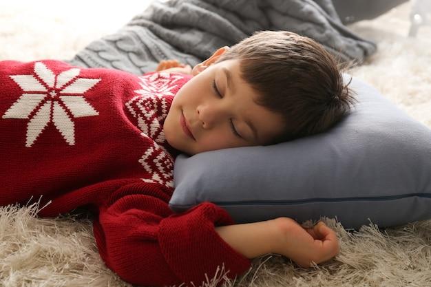 Ragazzino carino che dorme sul pavimento a casa