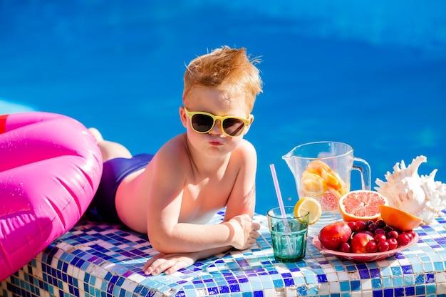 Ragazzino sveglio in occhiali da sole e costume da bagno beve limonata a bordo piscina.