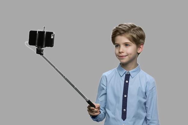 Ragazzino sveglio utilizzando selfie stick. bel bambino con il monopiede di scattare una foto su sfondo grigio. bambini e concetto di tecnologia moderna.