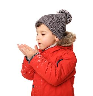 Ragazzino carino in vestiti caldi che gioca con lo sfondo della neve