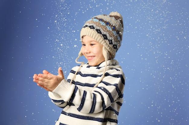 Ragazzino carino in vestiti caldi che gioca con la neve su uno sfondo colorato